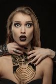 stock photo of gothic hair  - Portrait of a gothic woman with hands of vampire on her neck on black background - JPG