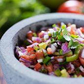 stone molcajete with mexican pico de gallo salsa close up