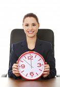Happy businesswoman holding a big clock