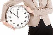Businesswoman holding a big clock
