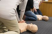 stock photo of cpr  - A group of adult education students practitcing CPR chest compressioon on a dummy - JPG