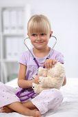 Little girl is examining her teddy bear using stethoscope, isolated