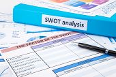 stock photo of swot analysis  - Blue binder SWOT analysis documents and graph report concept for business planning and evaluation - JPG