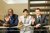 happy businesspeople waving hands in office