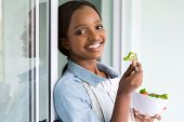 beautiful african girl eating salad at home