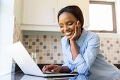 happy young african woman using laptop at home