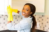 beautiful african woman cleaning cupboard