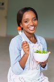 attractive african woman eating fresh green salad at home