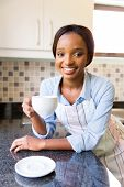 attractive young african woman having cup of coffee in the kitchen