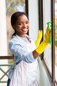 portrait of happy african girl cleaning window glass