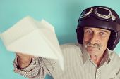 Aged funny man as a pilot with hat and glasses using paper plane