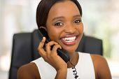 portrait of young african office worker using telephone in office