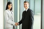 happy business partners handshaking in conference hall
