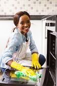 pretty african girl cleaning stove at home