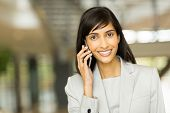 cheerful indian business executive talking on cell phone