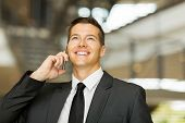 cheerful male corporate worker talking on cell phone