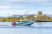 PUNO, PERU, MAY 5, 2014: Inhabitant of Uros Islands travels by boat between islands