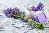 Lavender bunch with soap and grinder on white wood