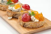 pic of apricot  - Blue cheese and apricot jam multigrain crostini with grapes and parsley on wooden tray - JPG