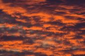 stock photo of wispy  - Vivid sky features sunset colors and wispy clouds - JPG
