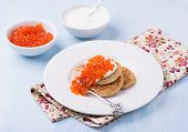 foto of buckwheat  - Buckwheat blini with red caviar and sour cream on white plate selective focus - JPG