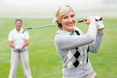 stock photo of ladies golf  - Lady golfer teeing off for the day watched by partner on a foggy day at the golf course - JPG