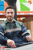 stock photo of forklift driver  - Smiling driver operating forklift machine in warehouse - JPG