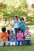 foto of pentecostal  - Children saying their prayers in park on a sunny day - JPG