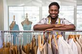 picture of racks  - Portrait of male fashion designer leaning on rack of clothes - JPG