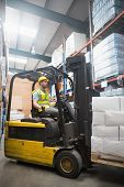 image of forklift driver  - Focused driver operating forklift machine in warehouse - JPG