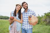 pic of farmer  - Happy farmers holding chicken and eggs on a sunny day - JPG