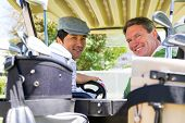 image of buggy  - Golfing friends driving in their golf buggy smiling at camera at the golf course - JPG