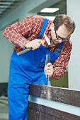 picture of chisel  - carpenter installer works with hammer and chisel at interior wood door installation - JPG