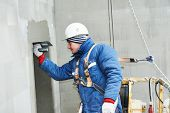 pic of putty  - builder at facade plastering work during industrial building with putty knife float - JPG