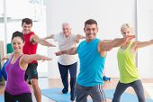 picture of senior class  - Happy men and women doing warrior pose in yoga class - JPG