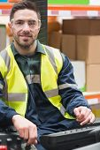 picture of forklift driver  - Smiling driver operating forklift machine in warehouse - JPG