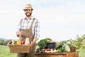 stock photo of farmer  - Farmer holding basket of vegetables at market on a sunny day - JPG