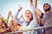 stock photo of excite  - Excited music fans up the front at a music festival - JPG