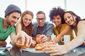 stock photo of crockery  - Fashion students eating doughnuts at the college - JPG