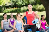 pic of yoga instructor  - Fitness group doing yoga in park on a sunny day - JPG