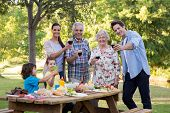 stock photo of extend  - Extended family having an outdoor lunch on a sunny day - JPG