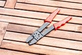 stock photo of stripper  - Background image of wire stripper on the wood table - JPG