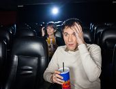 stock photo of movie theater  - Terrified people watching film in movie theater - JPG