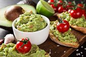 foto of avocado  - Guacamole with bread and avocado on stone background - JPG