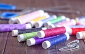 image of rayon  - color threads and scissors on the wooden table - JPG