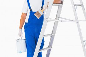 image of handyman  - Midsection of handyman with paintbrush and can on ladder over white background - JPG