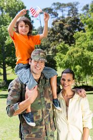 picture of reunited  - American soldier reunited with family on a sunny day - JPG