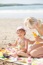 foto of children beach  - Crying little girl at the beach with her mother in the sun - JPG