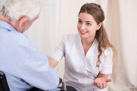 stock photo of nursing  - Nurse talking with elder man staying at residential home - JPG