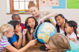 foto of globe  - Cute pupils and teacher in classroom with globe at the elementary school - JPG